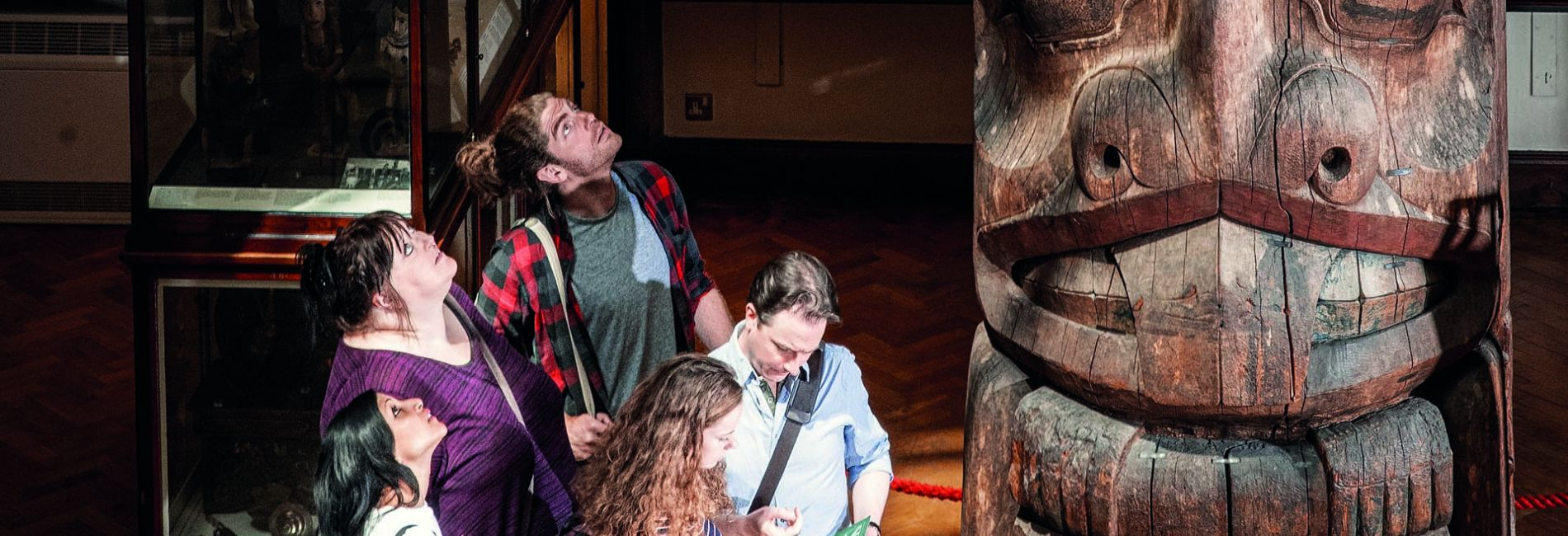 five people looking at a totem pole in the Museum of Archaeology and Anthropology
