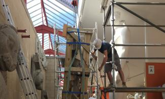 Conservator working on scaffold in museum
