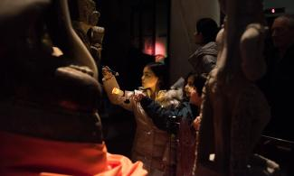 Children looking at a statue with their torches
