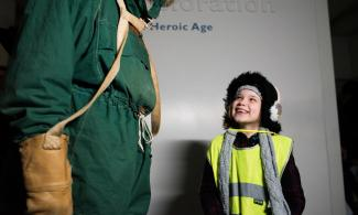 Girl smiling up at an Antarctic explorer
