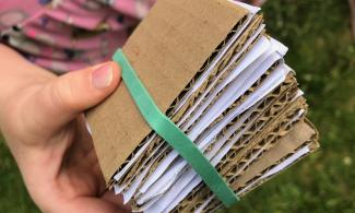 Image of child's hand holding a mini flower press made out of cardboard