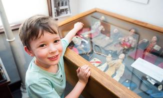 Little boy looking at a glass case of objects